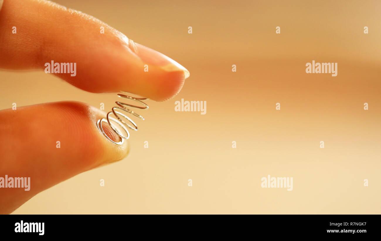 Un primerísimo plano de dedos deprimente, empujando un pequeño resorte de cromo. Tonto, miedo al concepto de ejercicio. Idea para la pérdida de peso, programa de ejercicios Imagen De Stock
