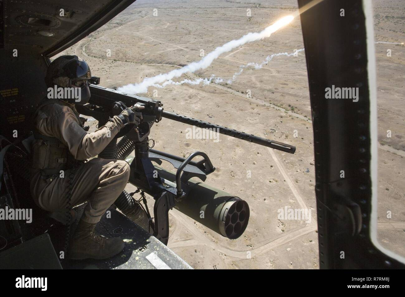 Cuerpo de Marines de EE.UU Cpl. Justin Gilstrap, un jefe de la tripulación con Luz Marina 167 escuadrón de helicópteros de ataque (HMLA-167), desencadena un GAU-21 calibre .50 ametralladora durante la artillería aérea perforadoras de refinamiento en chocolate Antena Montaña Tiro, California, 5 de abril de 2017. Armas y tácticas Instructor 2-17 es un evento de capacitación de siete semanas organizado por la Aviación Marina armas y tácticas de escuadrón MAWTS Uno (cuadro 1). Foto de stock
