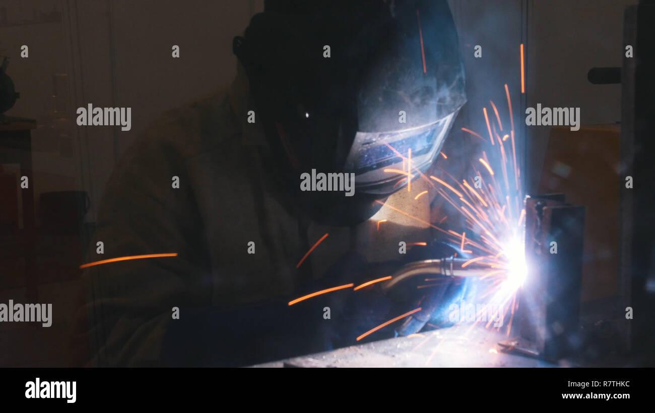 Un casco de soldador en hacer su trabajo. El proceso de soldadura. El humo y las chispas Foto de stock