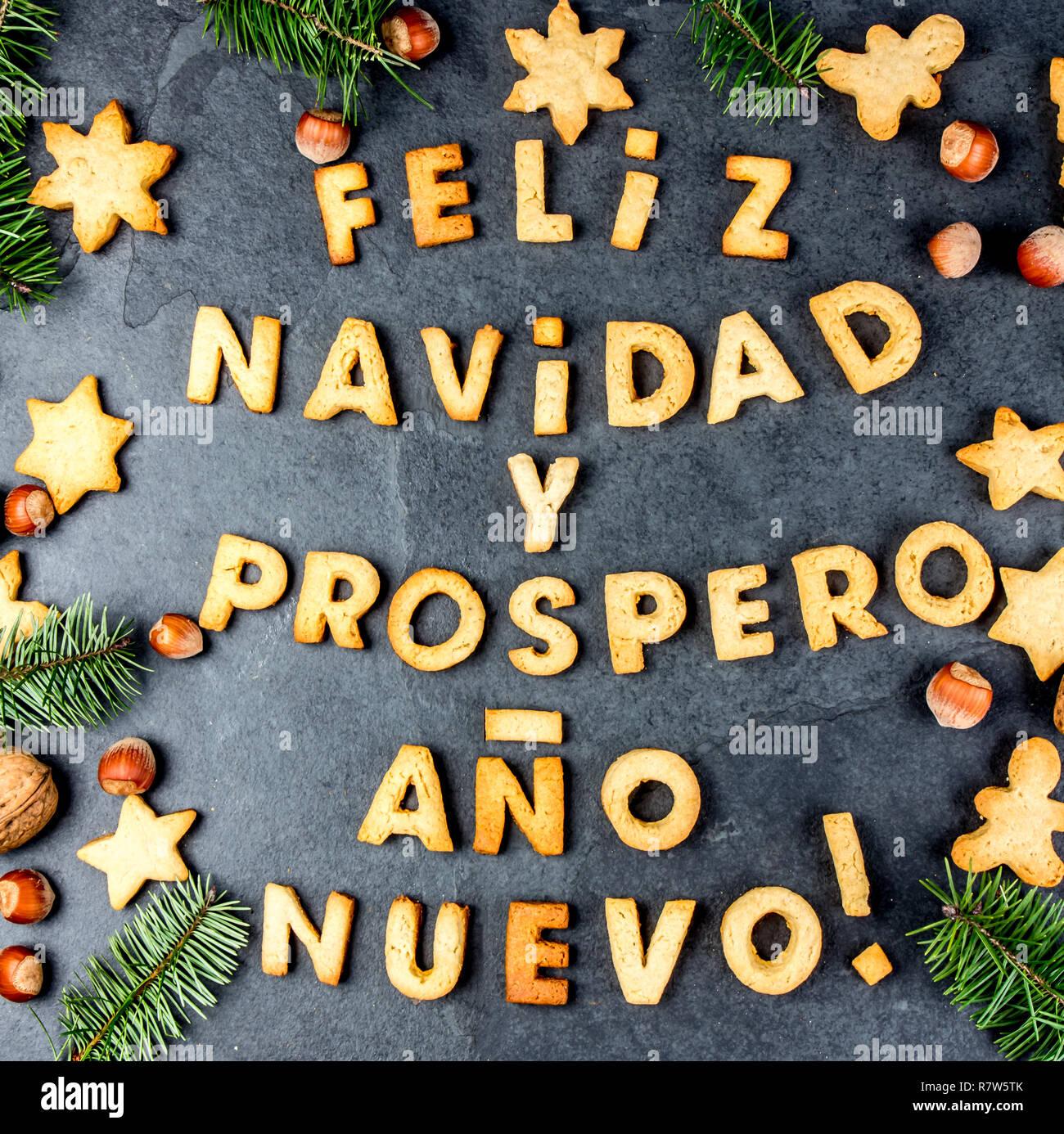 FELIZ NAVIDAD EN ESPAÑOL LAS COOKIES. Palabras Feliz Navidad y feliz año nuevo en Español con galletas, tarjeta de Navidad para los países de habla hispana vista desde arriba. Imagen De Stock