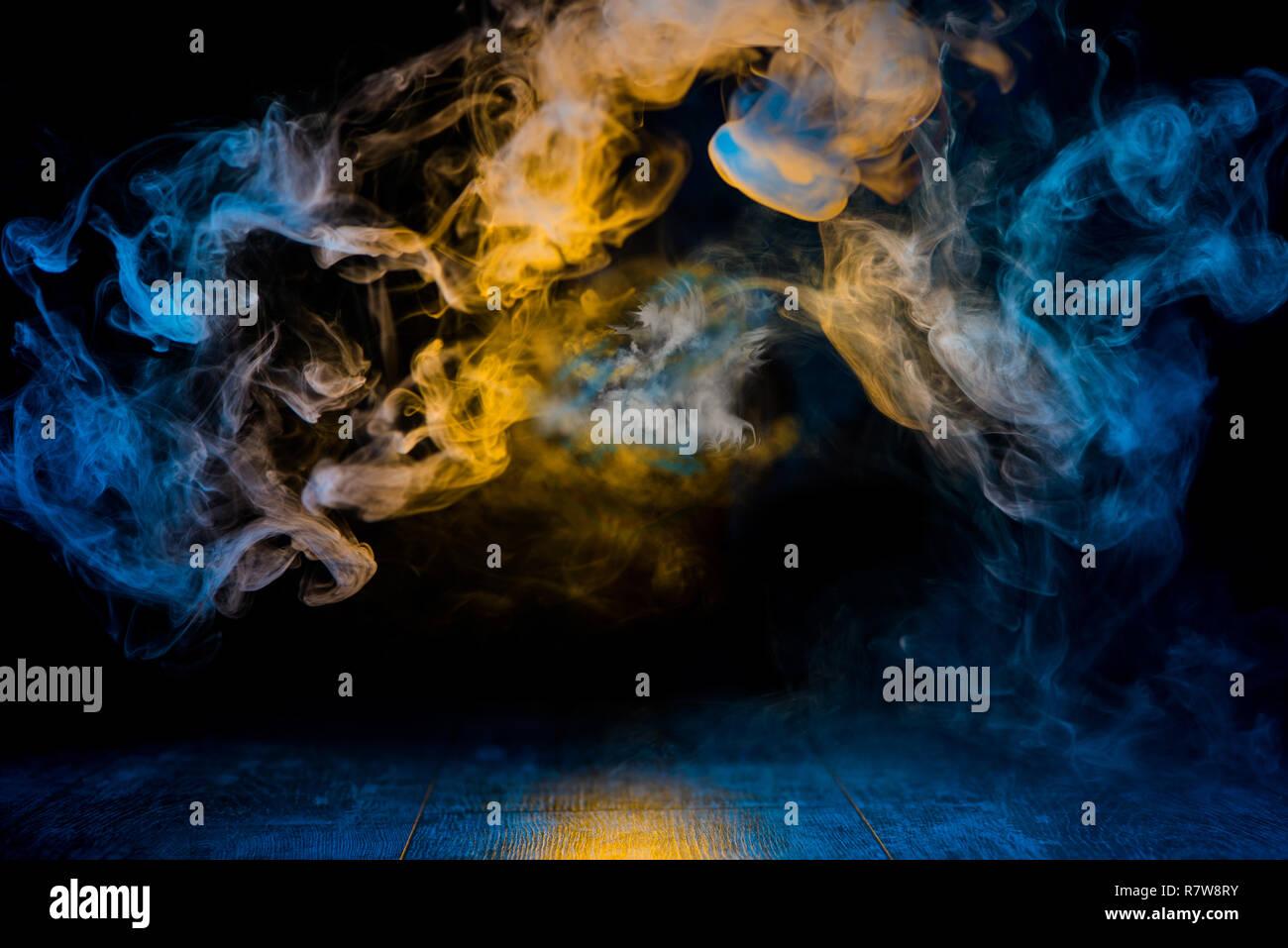 Patrones de humo amarillo y azul en fondo oscuro Imagen De Stock