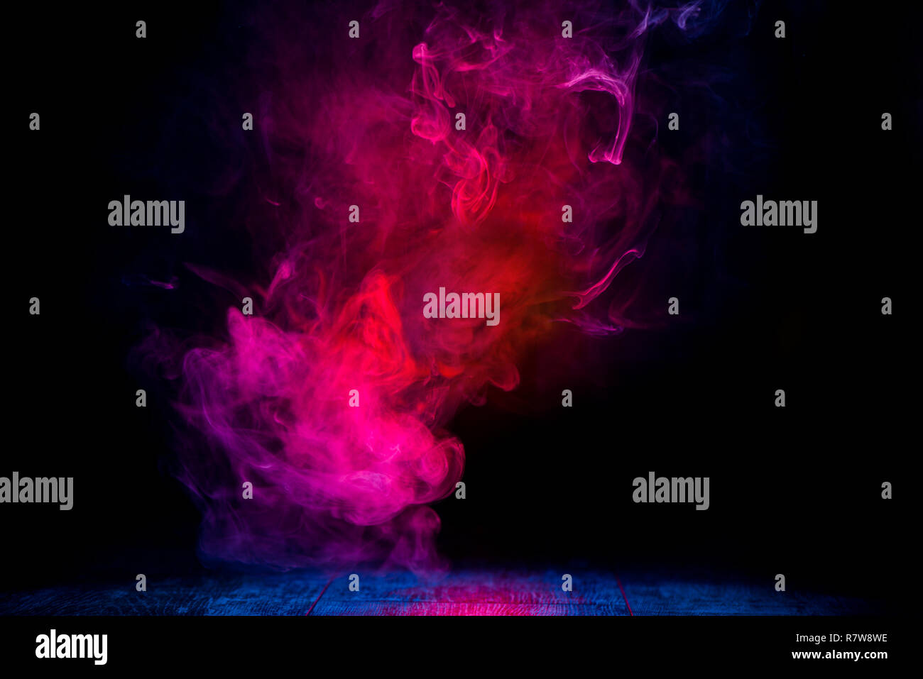 Patrones de humo rojo y azul en fondo oscuro Imagen De Stock