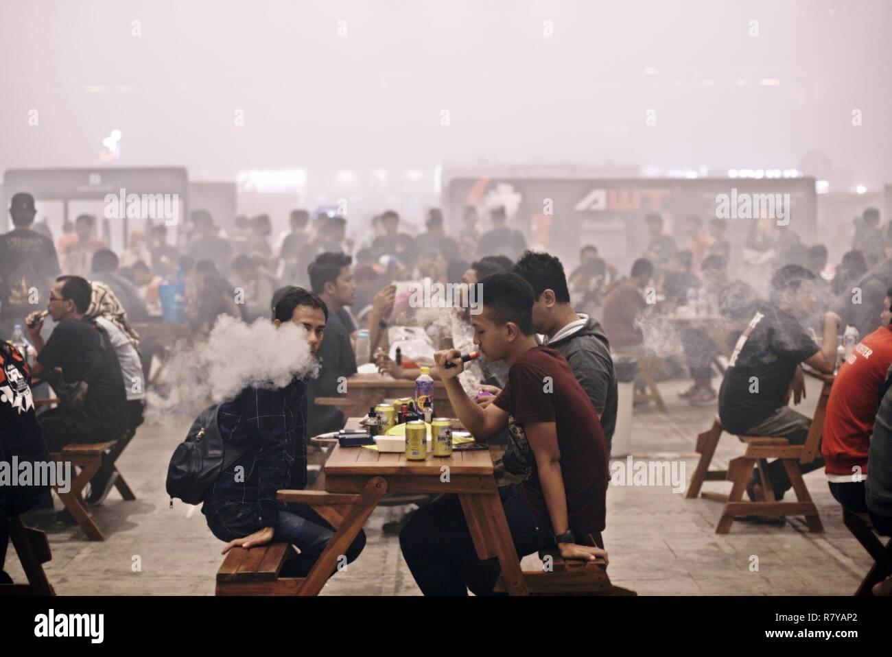 Los visitantes puff sobre sus e-cigarrillos después de las comidas durante el 2018 Vape feria Expo Internacional de Yakarta, Yakarta, Indonesia. © Reynold Sumayku Imagen De Stock