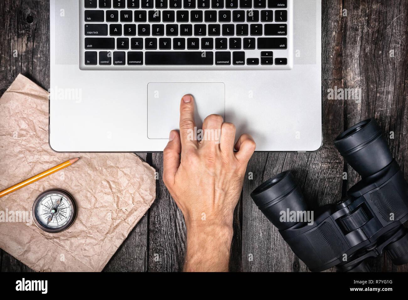 Viajero a preparar su viaje con un ordenador portátil, brújula y prismáticos en el fondo de madera Imagen De Stock