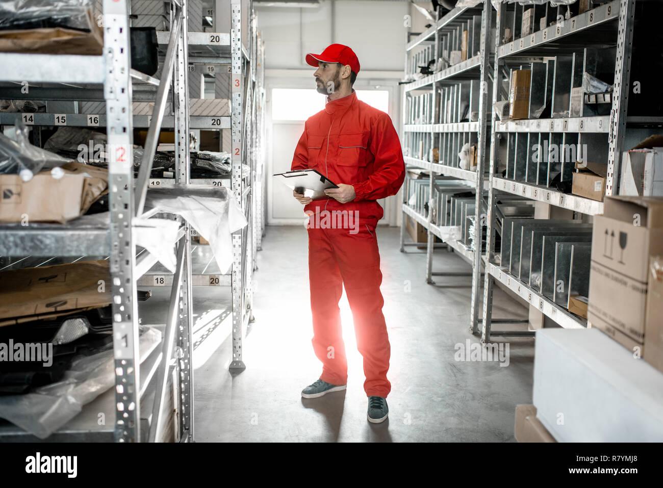Almacenamiento En Estanterias Metalicas.Trabajador De Almacen En Rojo Un Control Uniforme De Mercancias Con