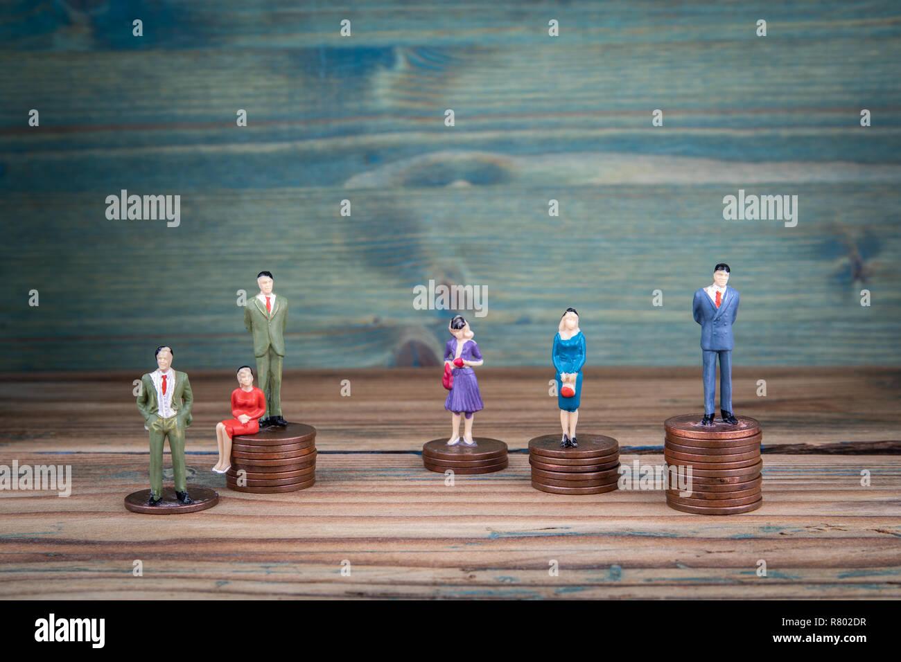 La gente de pie en miniatura en los montones de monedas Foto de stock