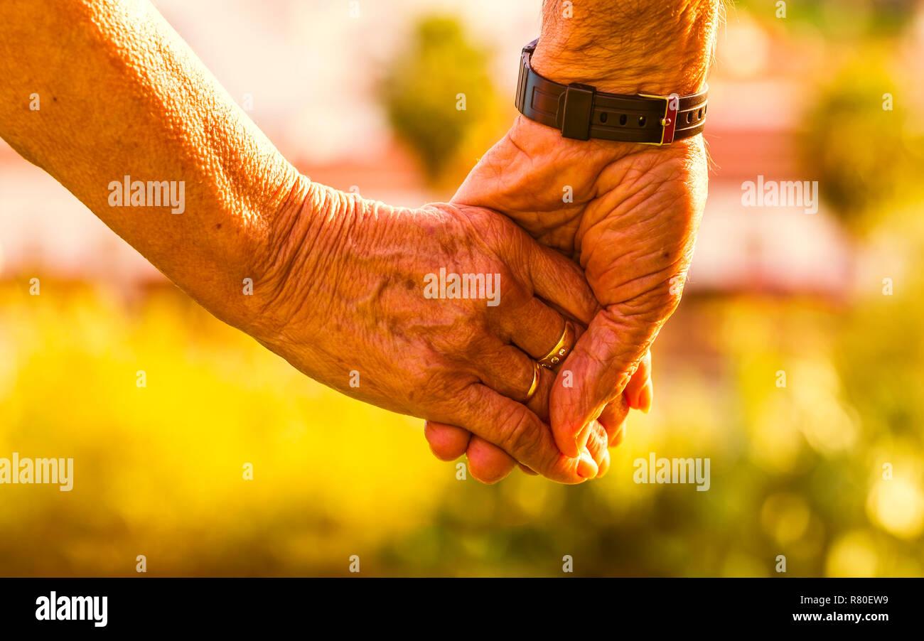 Captura recortada de la pareja de ancianos cogidos de la mano al atardecer al aire libre. Se centran en las manos Foto de stock