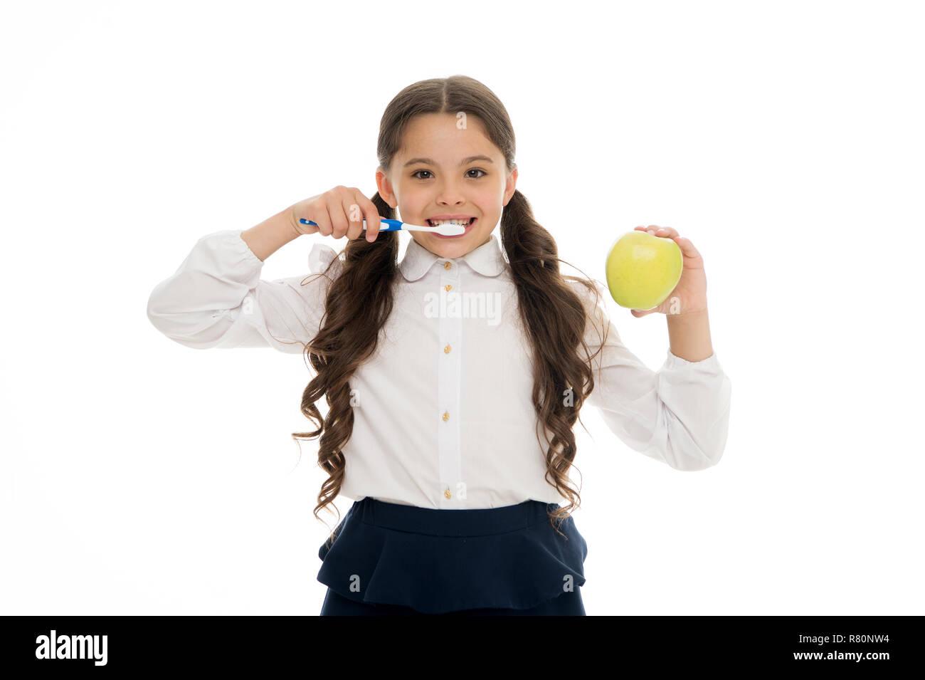 Cepillo de dientes cada día. Concepto de higiene oral. Chica mantenga el cepillo de dientes y apple fondo blanco. Niño Niña mantenga frutas y cepillo con pasta de dientes. Niño schoolgirl kid feliz diente cuidado de la higiene bucal. Imagen De Stock