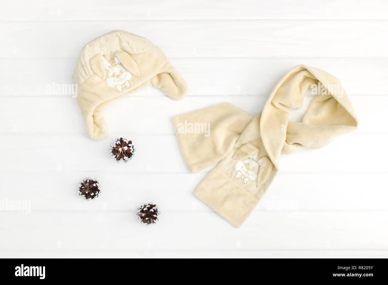 El otoño o invierno ropa de moda. Bebé ropa de color beige en el fondo de madera. Imagen De Stock