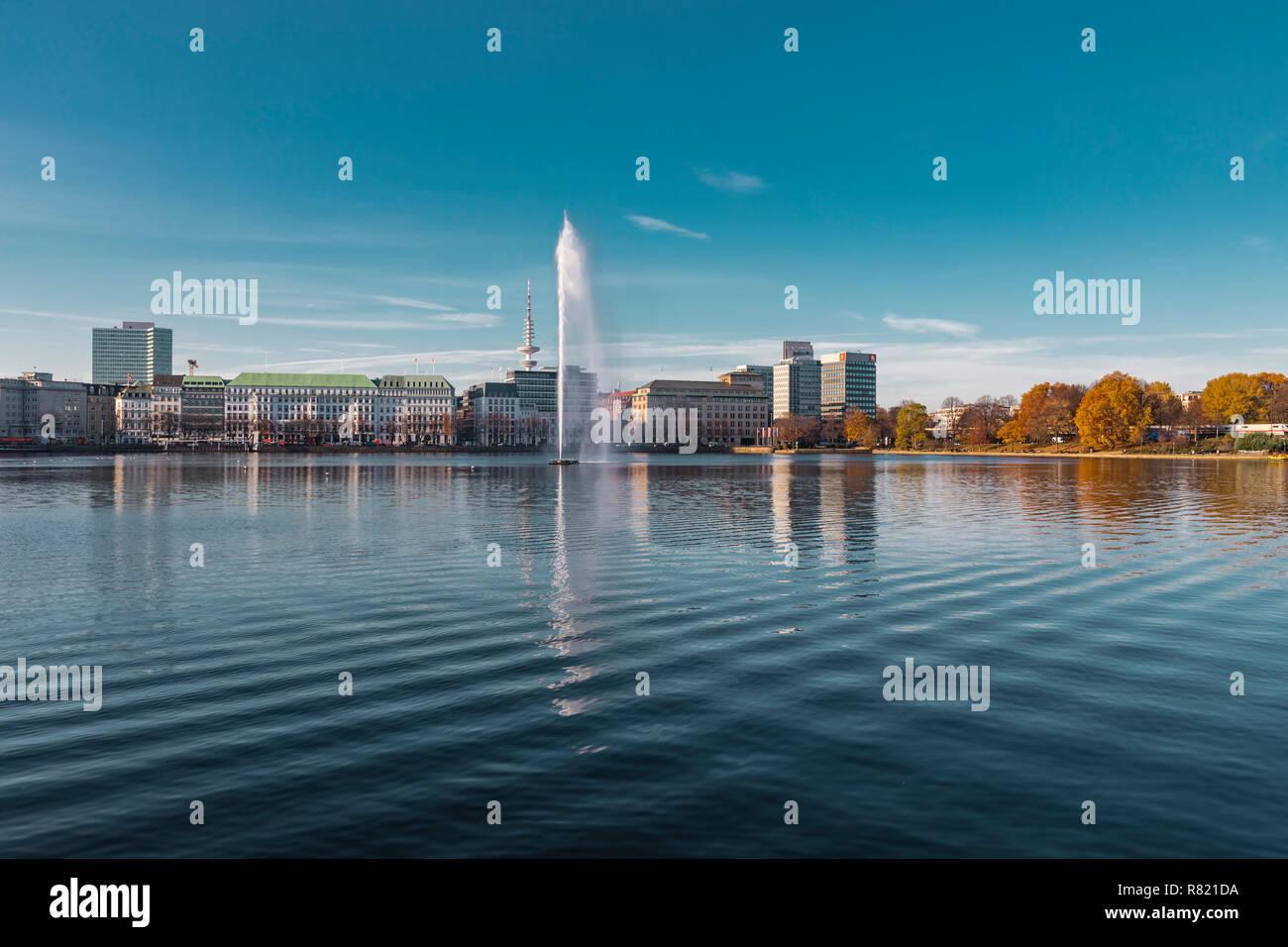 Hamburgo, Alemania - Noviembre 15, 2018: Vista del Binnenalster y su fuente en la ciudad de Hamburgo en Alemania, con el cielo azul como fondo. Foto de stock