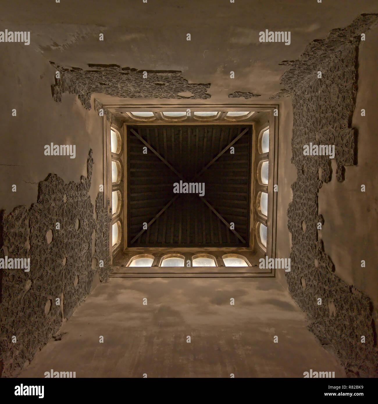 Ángulo bajo vista centrada en el interior de una torre, de palacio nazarí, con restos de tallas de piedra decorativa y ventanas de arco en la parte superior Alhamb Foto de stock