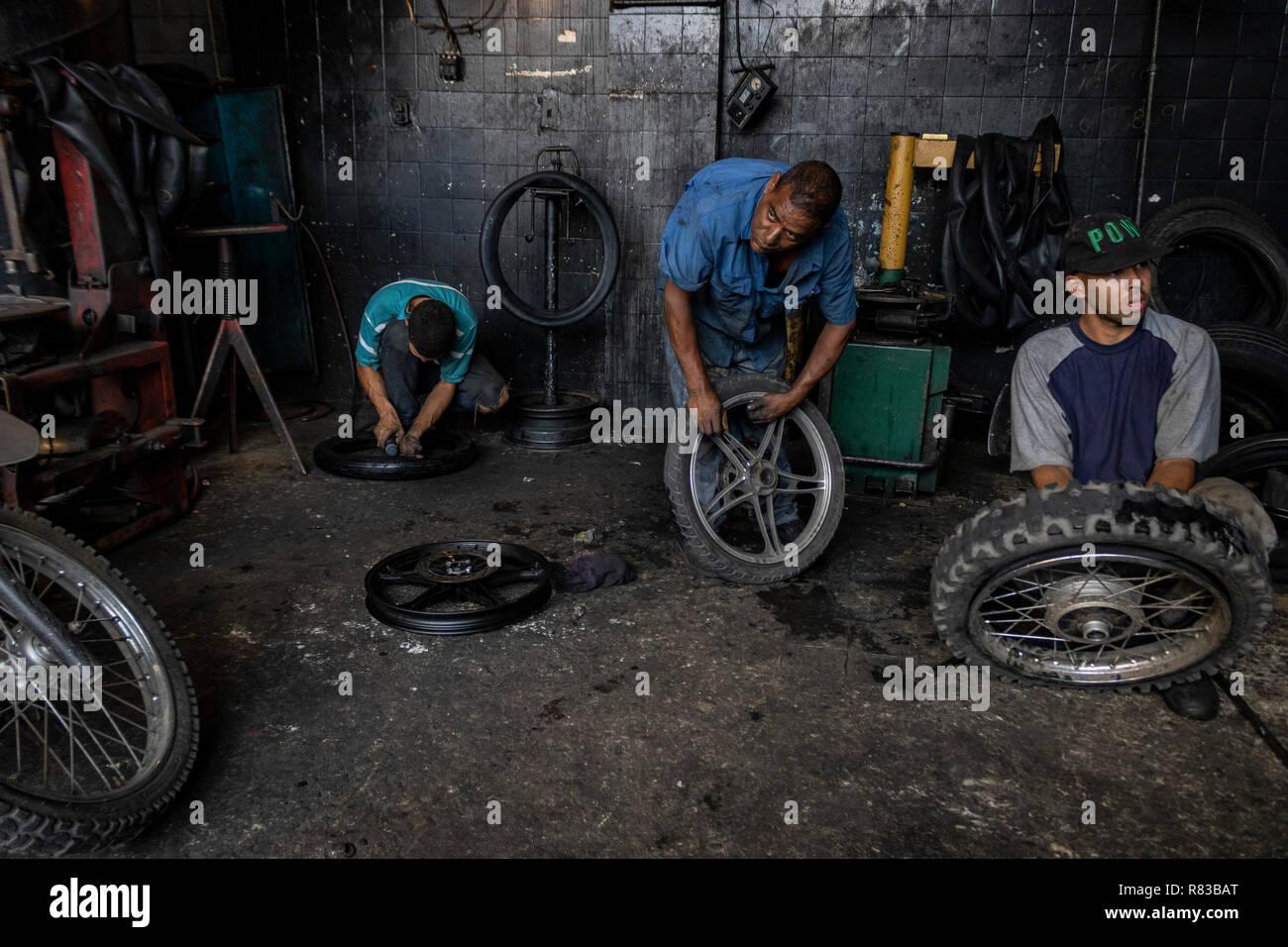 Caracas, Venezuela. 11 Dec, 2018. Los venezolanos abrigos de reparación en un taller. En vista de la crisis económica, todo en Venezuela está siendo reparado hasta es absolutamente inútil. El mercado interno venezolano está sufriendo enormemente debido a la crisis económica. Según el Fondo Monetario Internacional (FMI), el país sudamericano se encamina a una inflación de 1,37 millones por ciento en 2018. Crédito: Rayner Peña/dpa/Alamy Live News Foto de stock