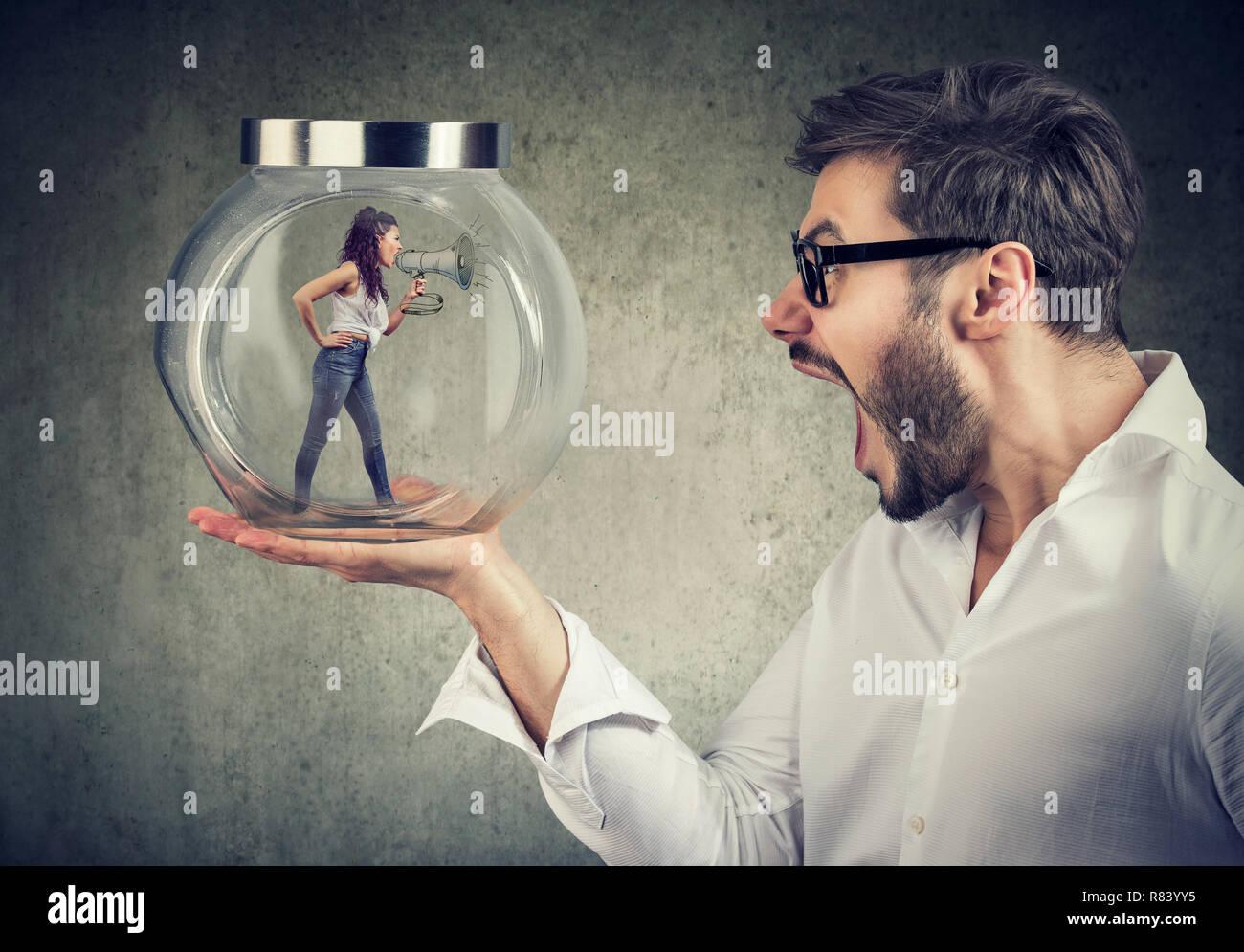 Frustrado empresario sosteniendo un frasco de vidrio con una furiosa gritando mujer atrapada en ti Foto de stock