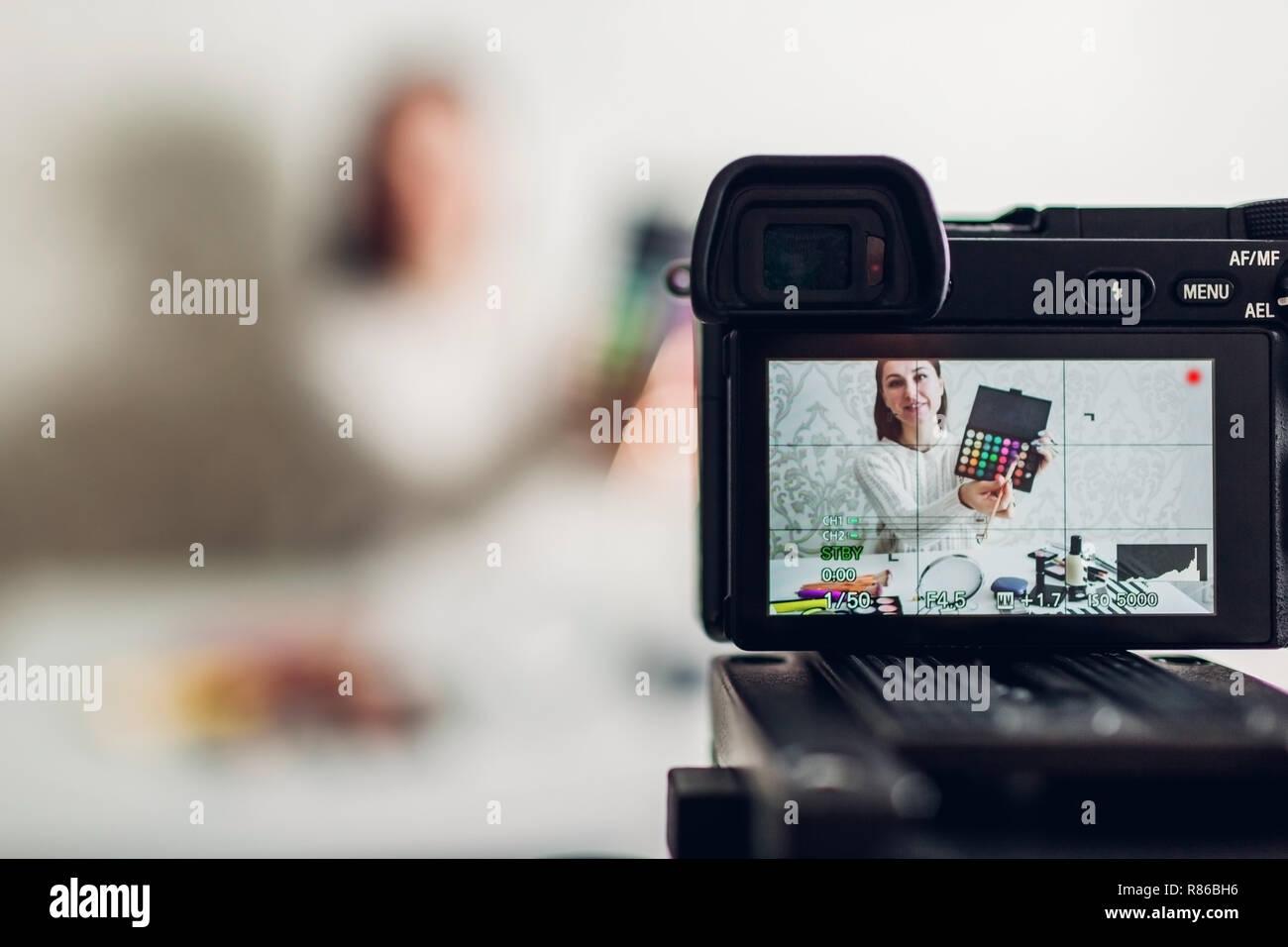 Mujer joven belleza profesional vlogger o blogger maquillaje tutorial de grabación con cámara y trípode en casa Foto de stock