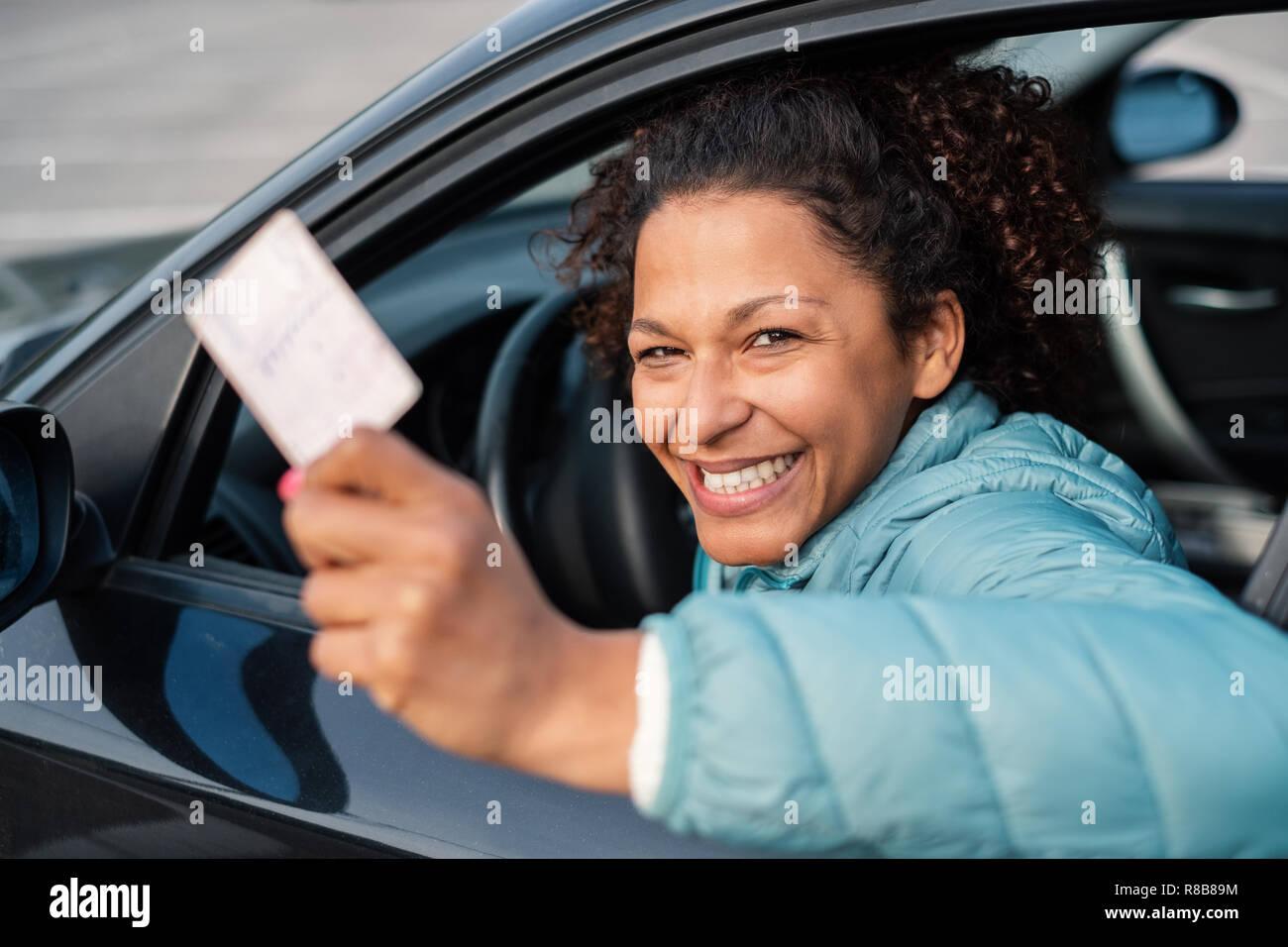 Conductor de coche negro mujer sonriente que muestran la nueva licencia de conductor Imagen De Stock