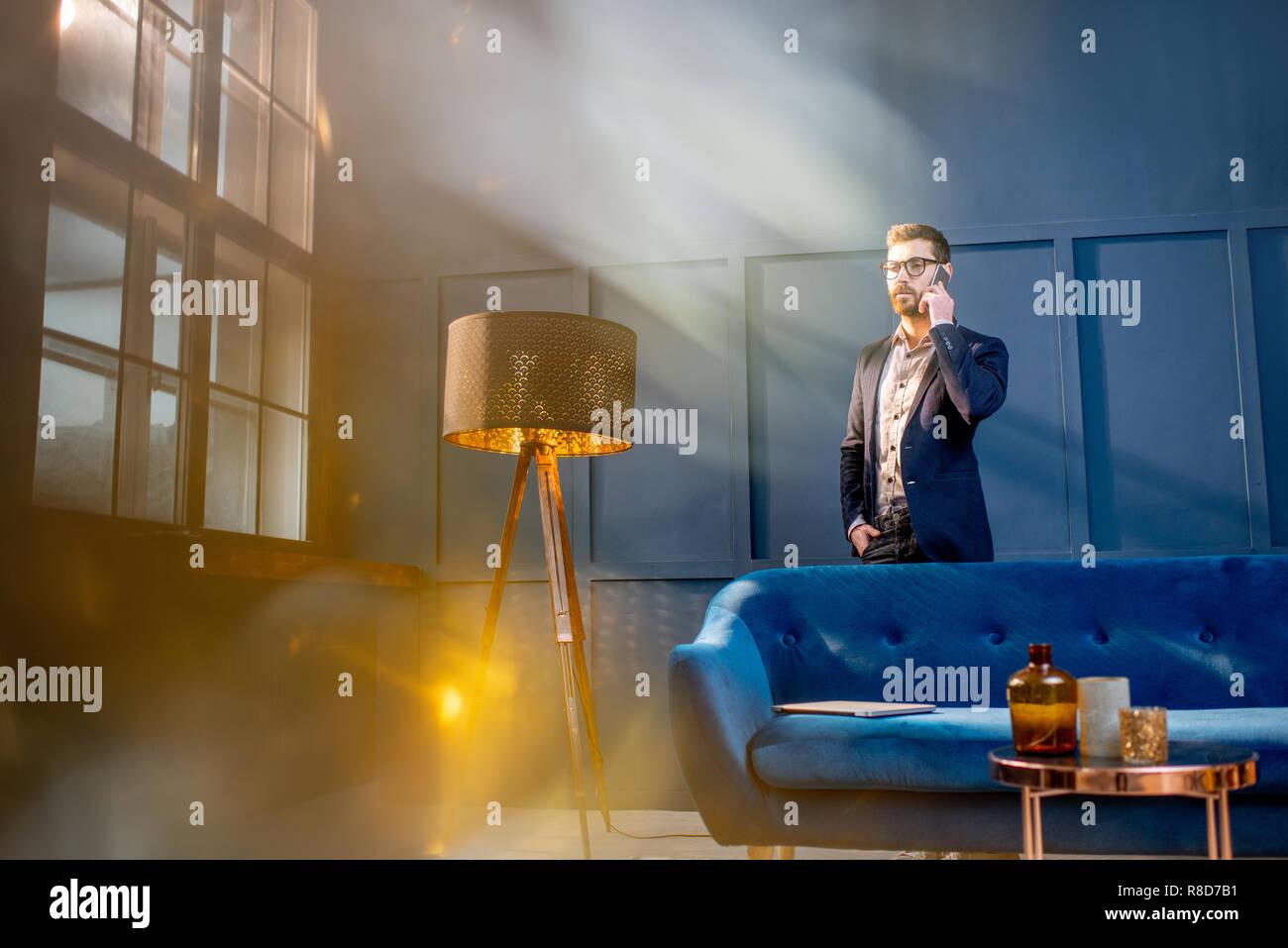 Retrato de un hombre de negocios elegante con laptop sentado en el sofá de su casa en el lujoso interior oficina azul Foto de stock