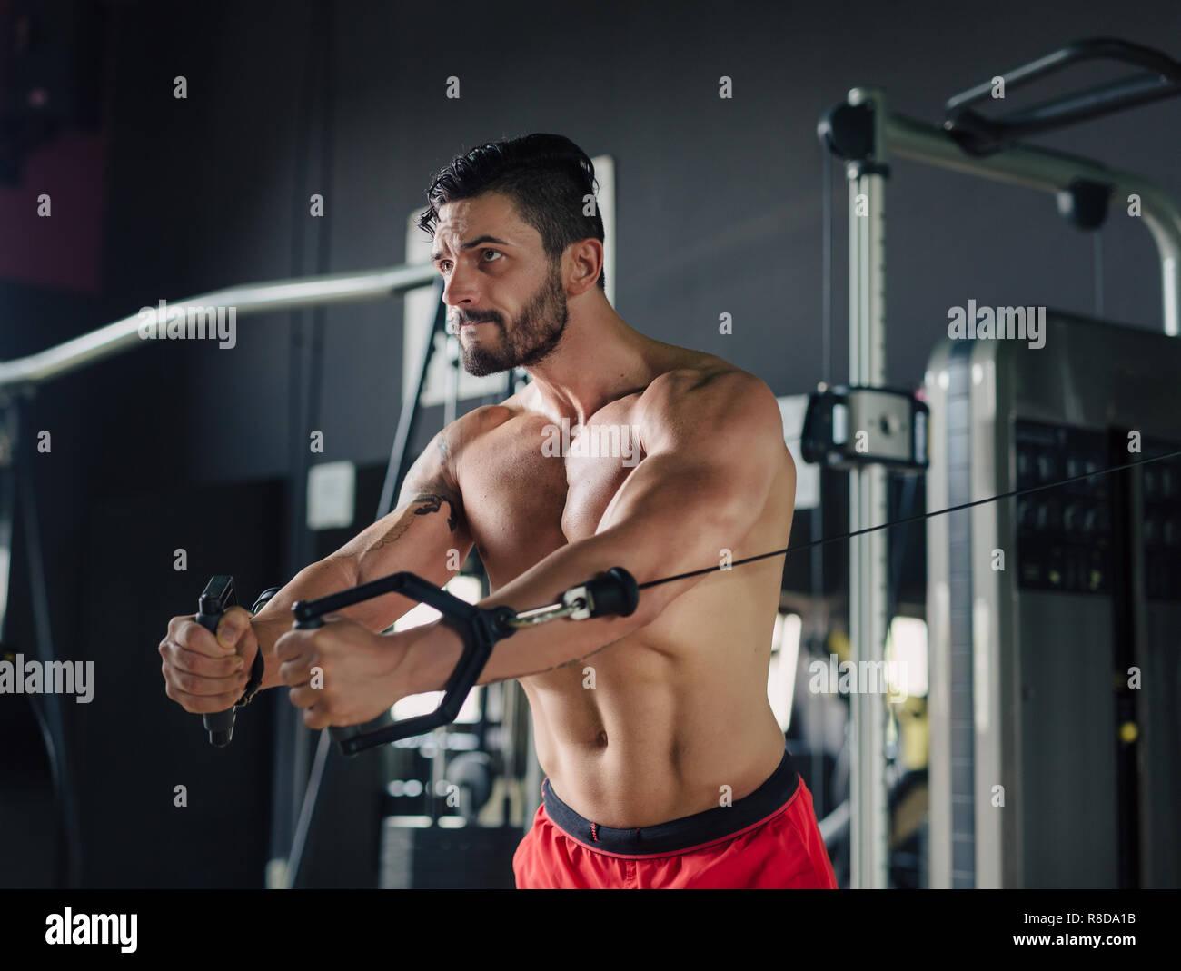 Hombre Fuerte en el gimnasio haciendo ejercicios de pecho Imagen De Stock