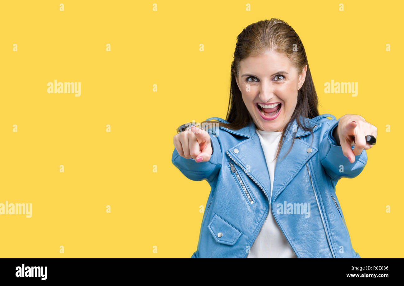Hermosa mujer madura edad media vistiendo chaqueta de cuero de moda sobre fondo aislado apuntando hacia usted y la cámara con los dedos, sonriendo positiv Imagen De Stock
