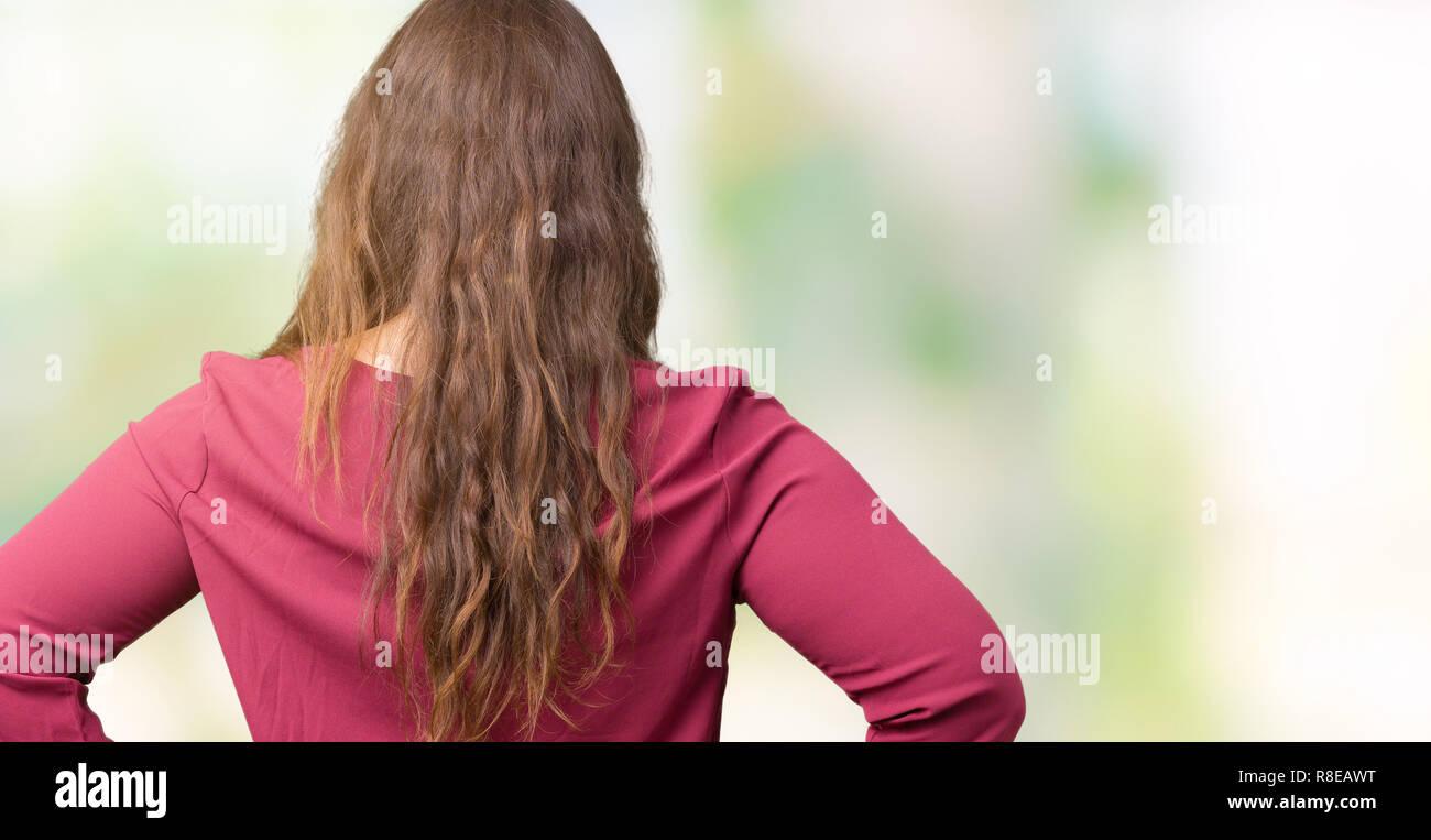 Hermosa joven plus size sobre antecedentes aislados de pie mirando hacia atrás lejos con los brazos sobre el cuerpo Imagen De Stock