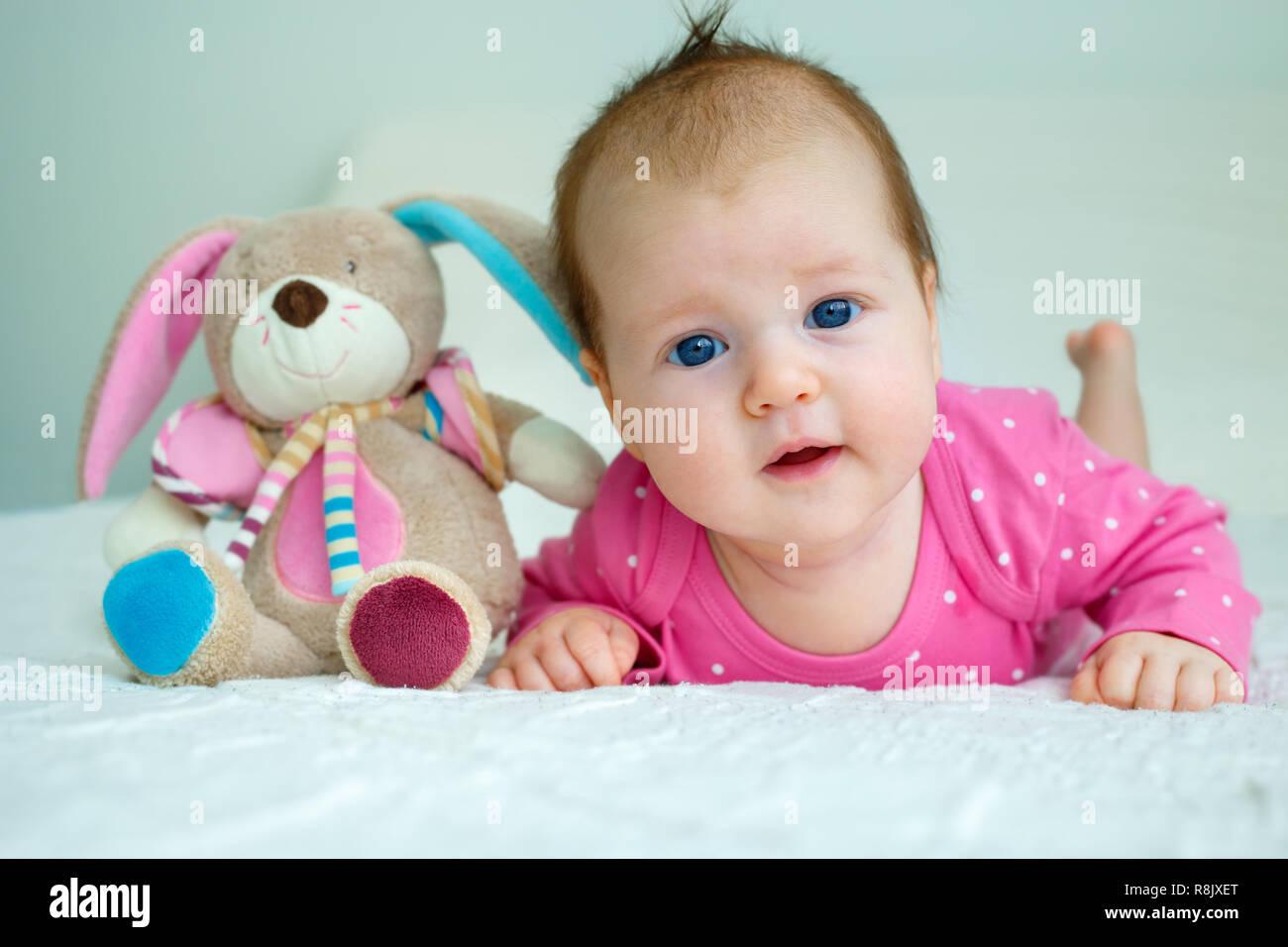 Retrato de un lindo bebé niña acostada sobre su estómago Imagen De Stock 852d87f5150