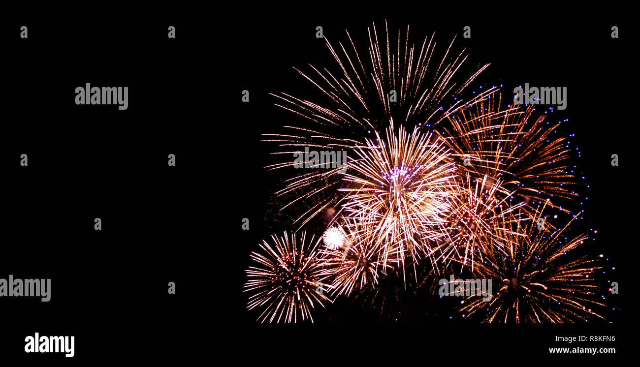 Y el festival de aniversario de fuegos artificiales en el cielo negro de noche con bellos fondos. Foto de stock