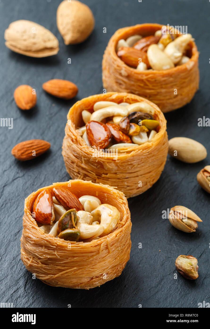 Tradicionales dulces de Oriente Medio 'nido de pájaro' en miel, jarabe con tuerca llenado - almendras, anacardos y pistachos. Baklava cerca. Un delicioso postre. S Foto de stock