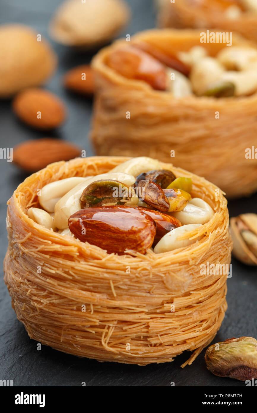 Tradicionales dulces de Oriente Medio 'nido de pájaro' en miel, jarabe con tuerca llenado - almendras, anacardos y pistachos. Baklava cerca. Delicioso postre Foto de stock