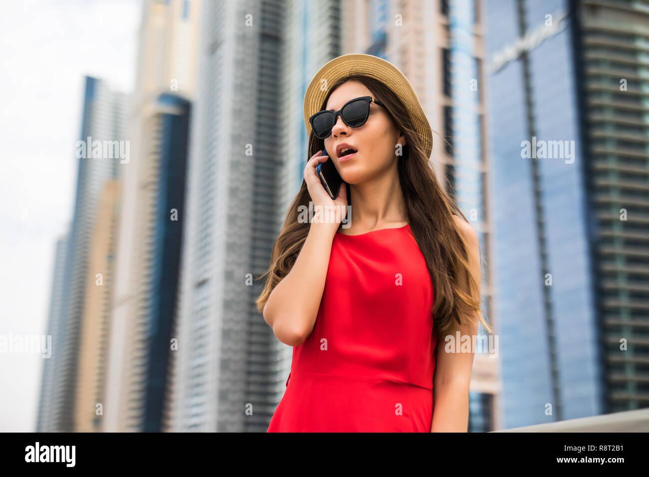 f230e3d477 Retrato de mujer joven en vestido rojo, gafas de sol y sombrero de verano  hablando