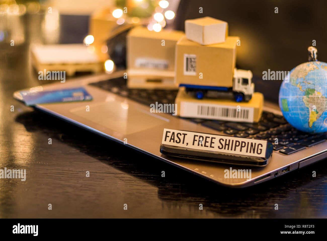 Rápido envío gratis - bodegón logística concepto de negocios con ordenador portátil, teléfono, mini cajas de envío Foto de stock