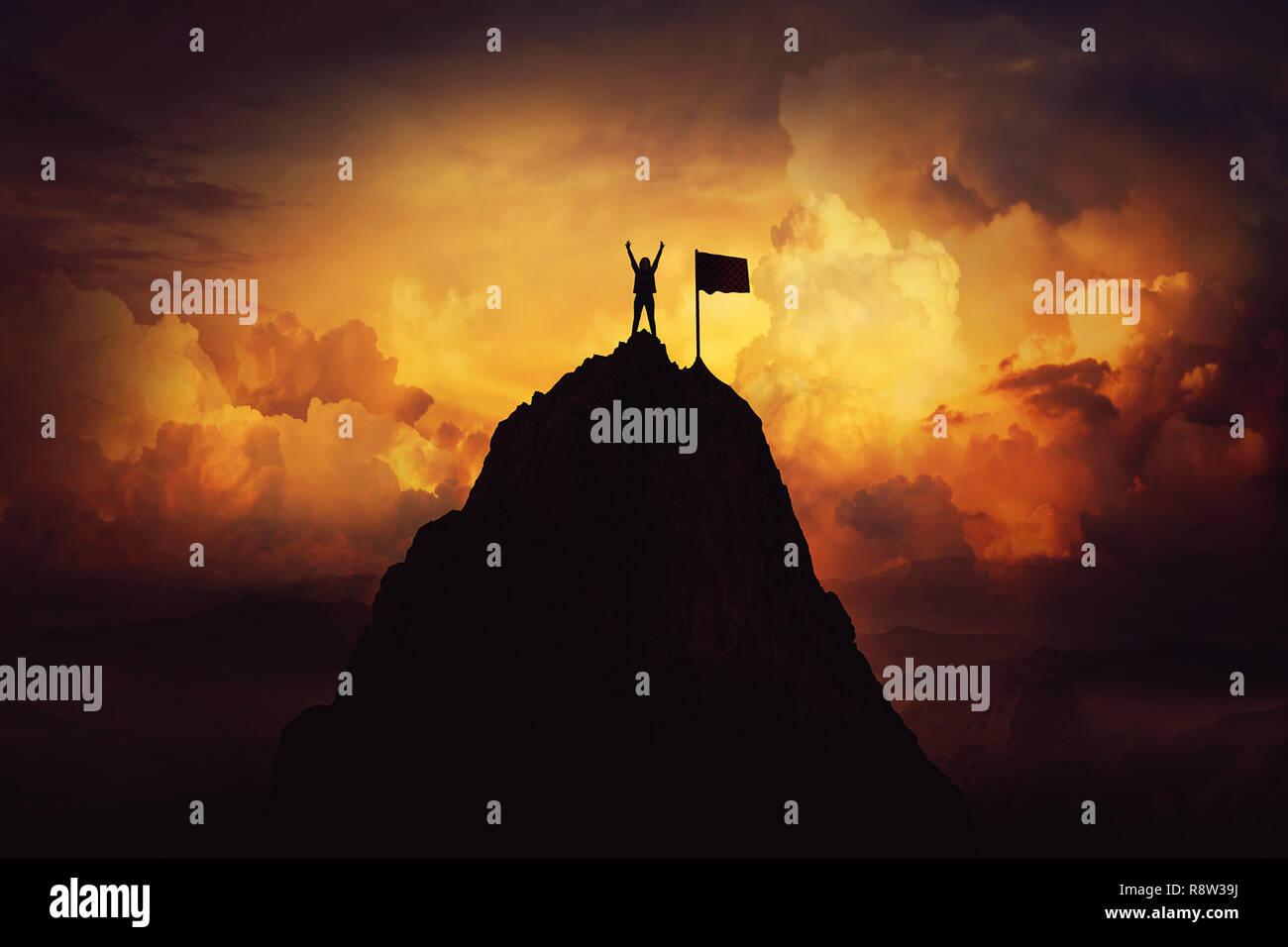Obstáculo a superar como una mujer levantar las manos arriba en la cima de una montaña, alcanzando la marca de final. Celebrar la victoria y éxito en el atardecer de fondo. G Imagen De Stock