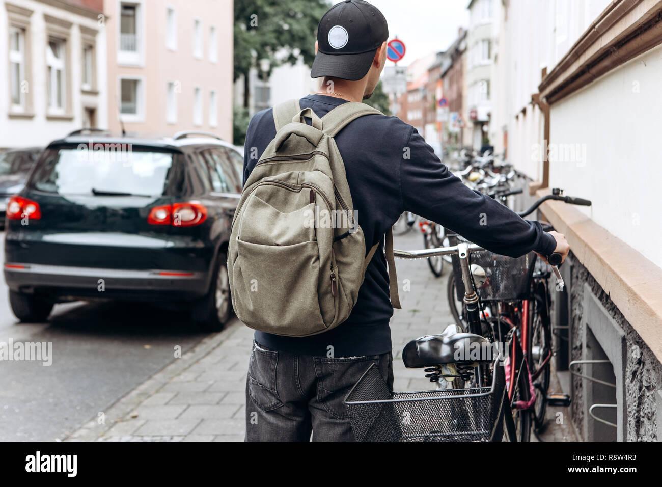 Turista o estudiante con una mochila va a montar una bicicleta. Foto de stock