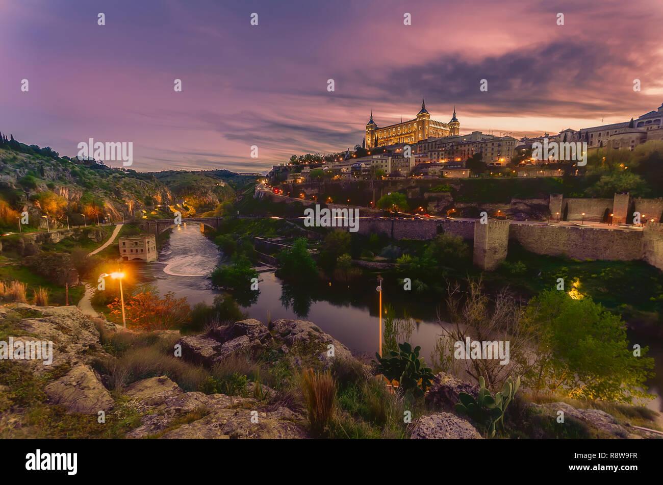 Toledo visto desde el otro lado del río Tajo al atardecer con el Alcázar de Toledo iluminada Foto de stock