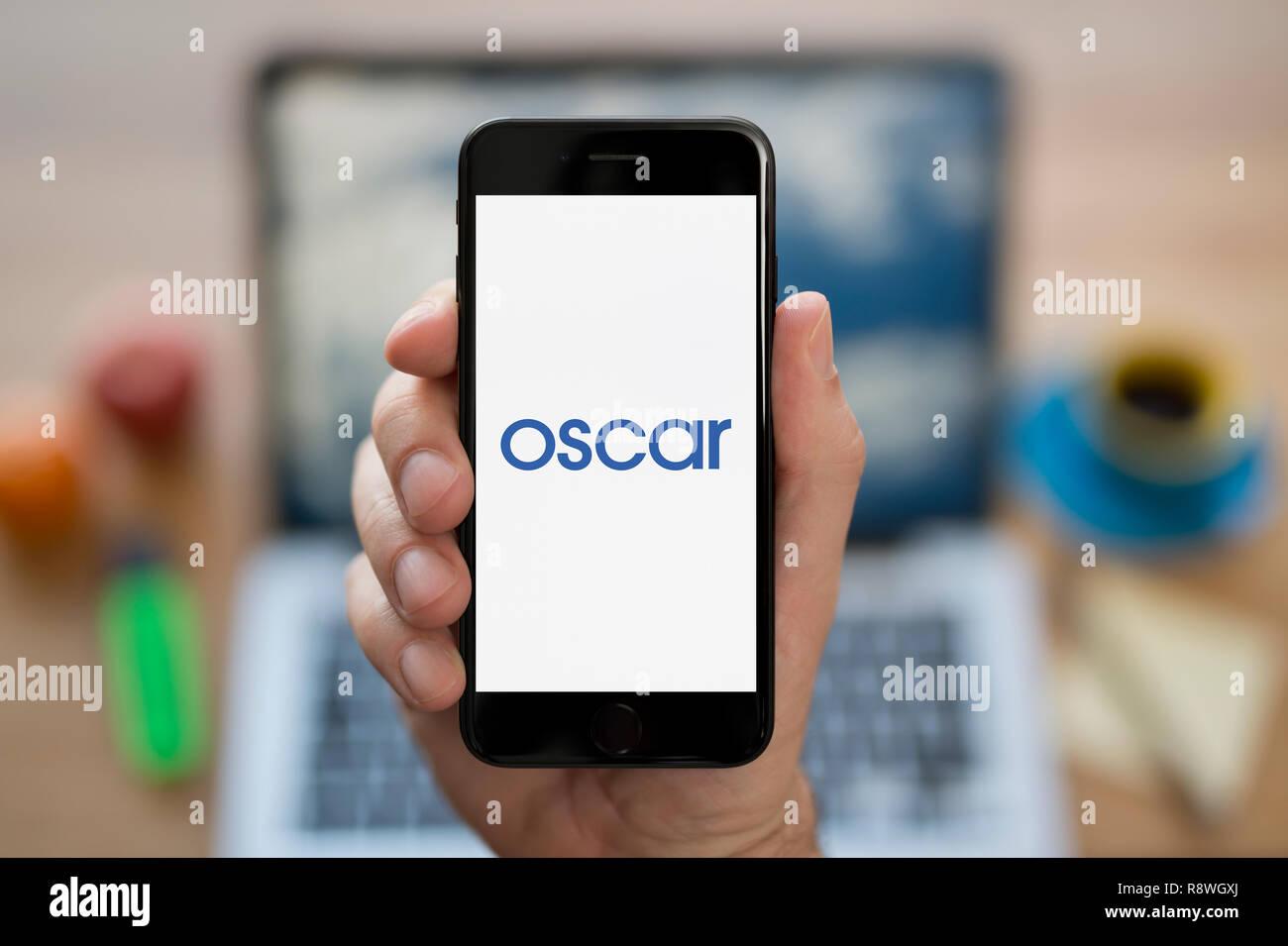 Un hombre mira el iPhone que muestra el logotipo de Oscar (uso Editorial solamente). Imagen De Stock