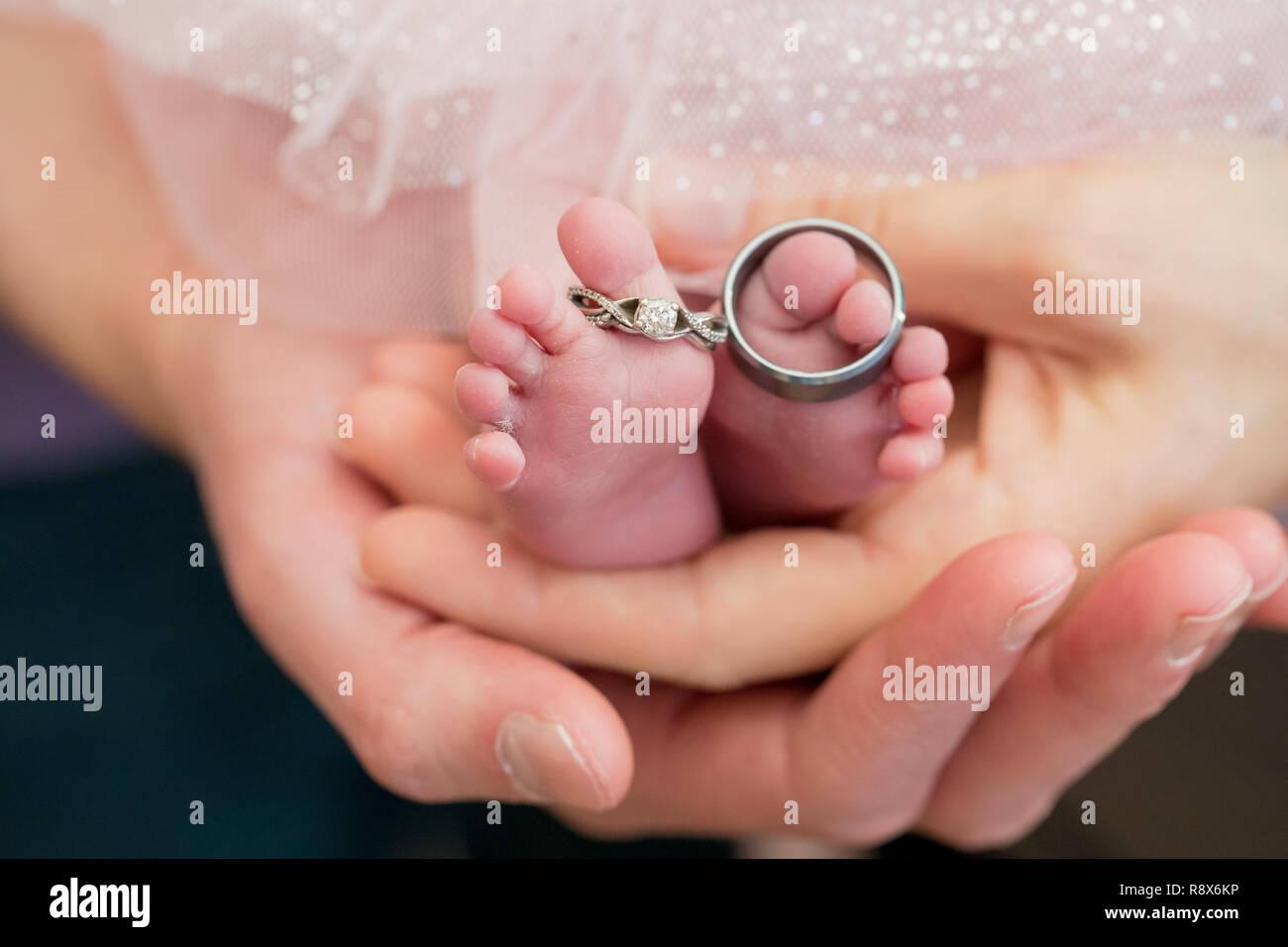 Un bebé recién nacido con pies regordetes sobre un cochecito