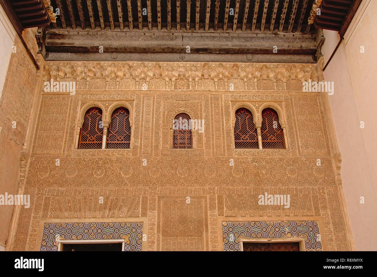 Pared con elaborar patrones decorativos y caligraphy orgánicos y ventanas con estrellas y otras formas, detalle del palacio nazarí , Alhambra, España Foto de stock