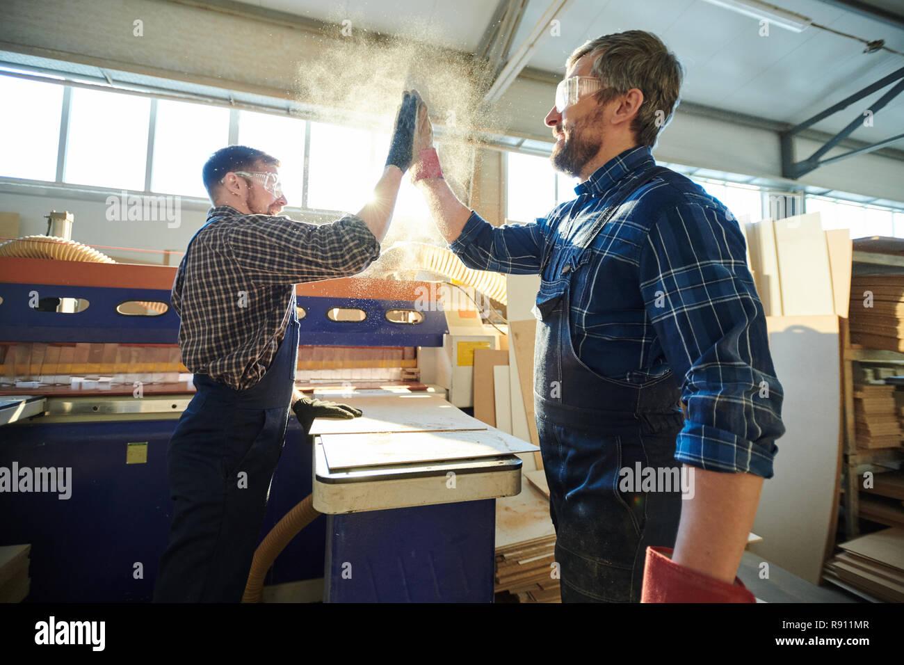 Satisfecho obreros haciendo High Five polvoriento Foto de stock