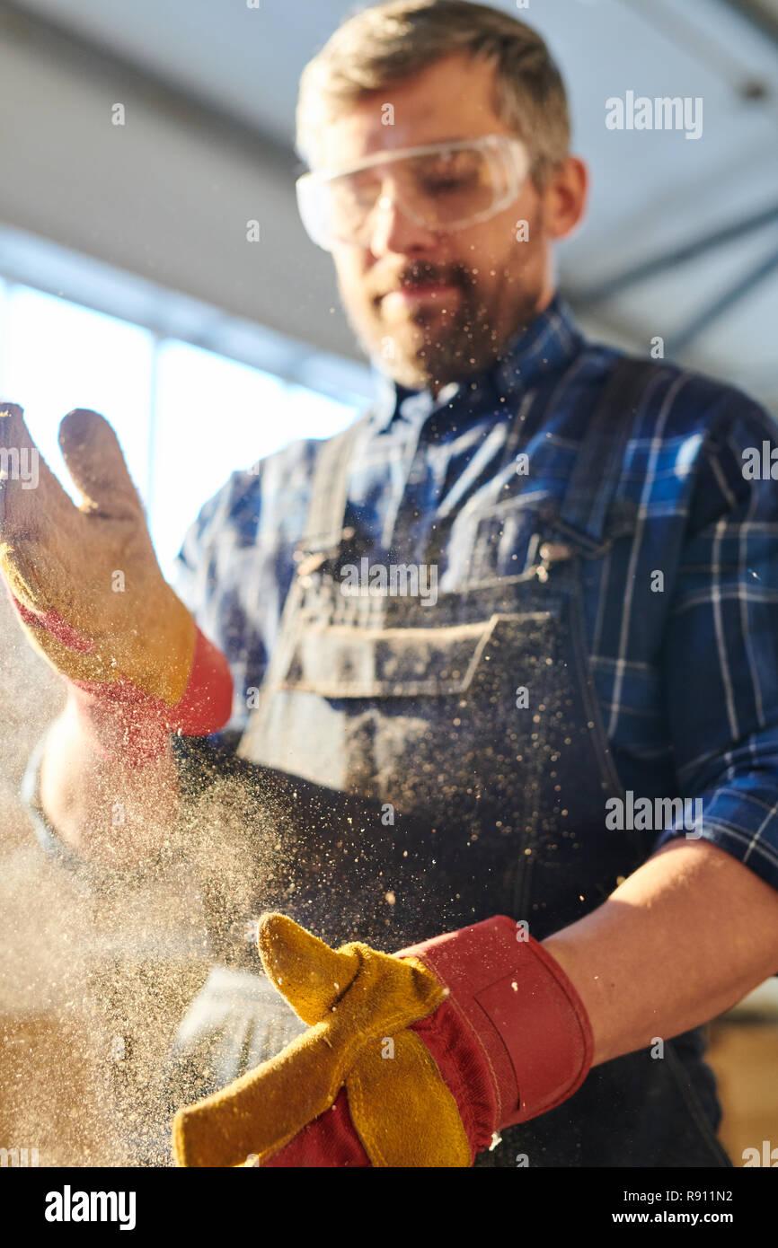 Workman dusting off manos Foto de stock
