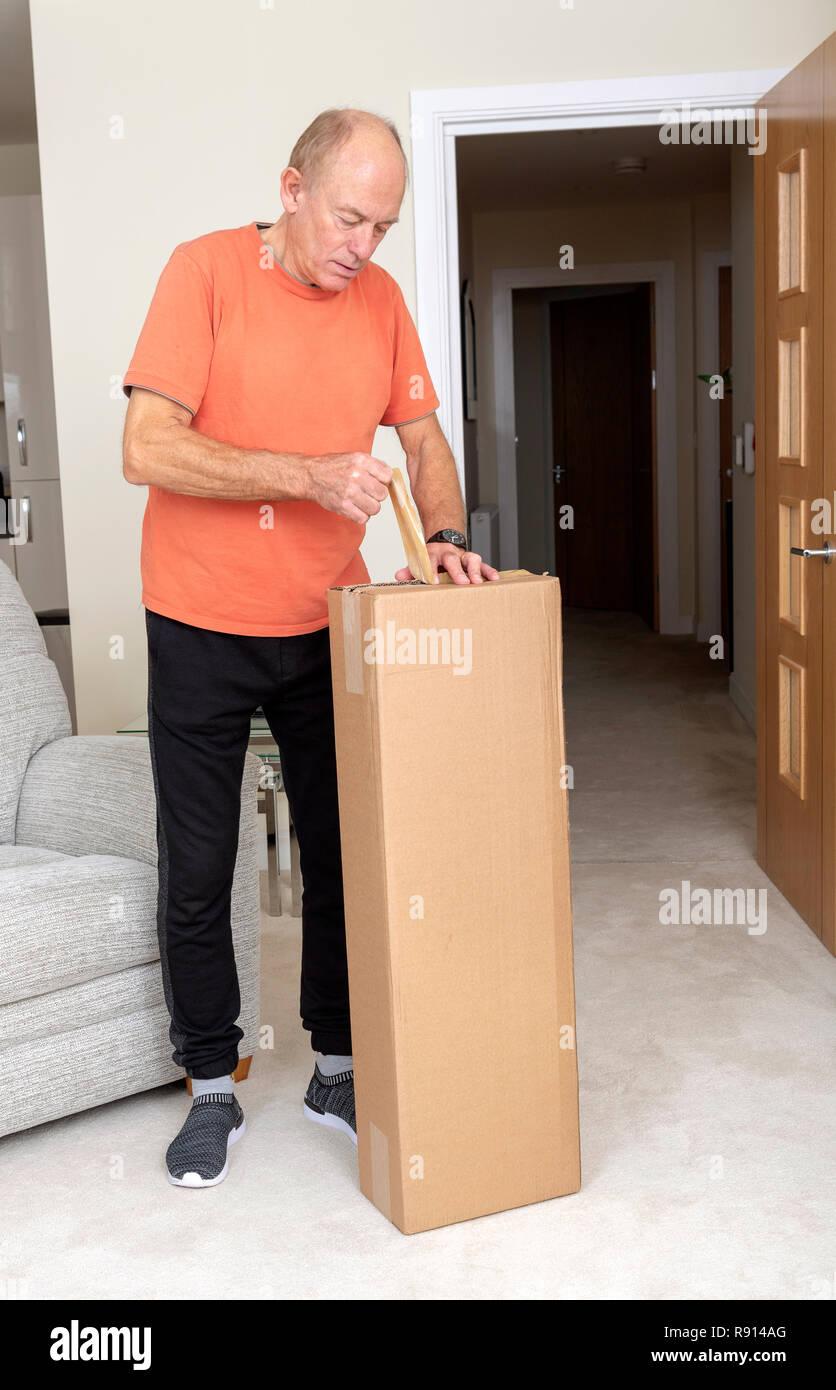 El hombre rompe la cinta adhesiva desde una bandeja de cartón marrón Imagen De Stock