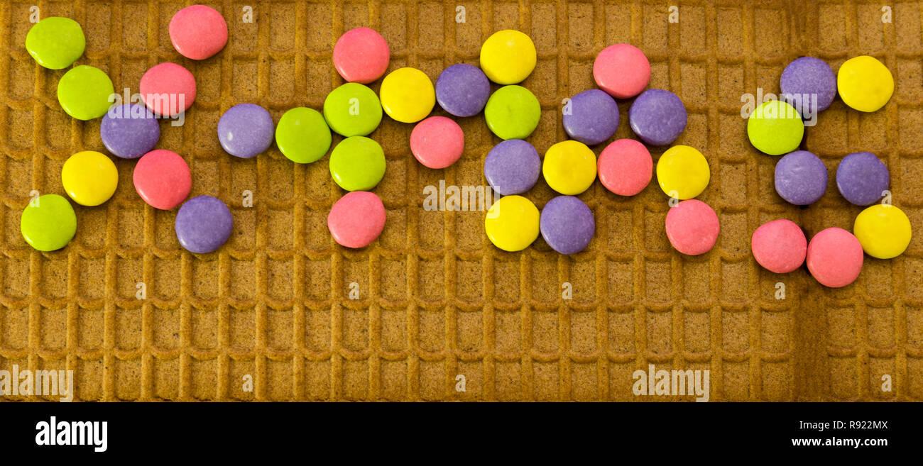 Multicolores de chocolate M&M Botones deletrear X-Mas en el techo de la casa de jengibre Imagen De Stock