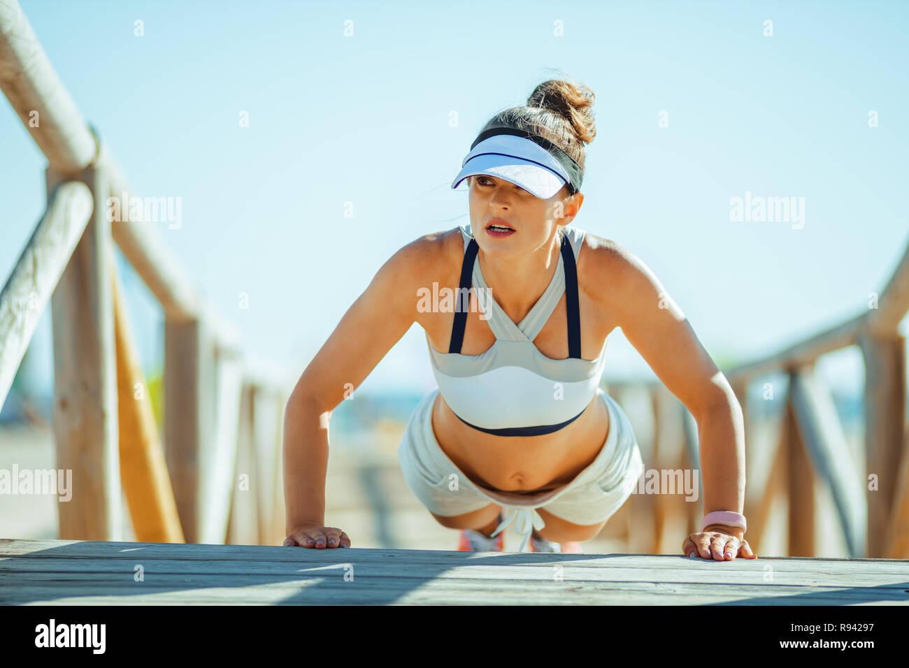 Colocar en el emparejador de mujer ropa de gimnasia en el Seacoast haciendo pushups. 30 años algo mujer fitness realizar programa fuerza y haciendo pushups Imagen De Stock