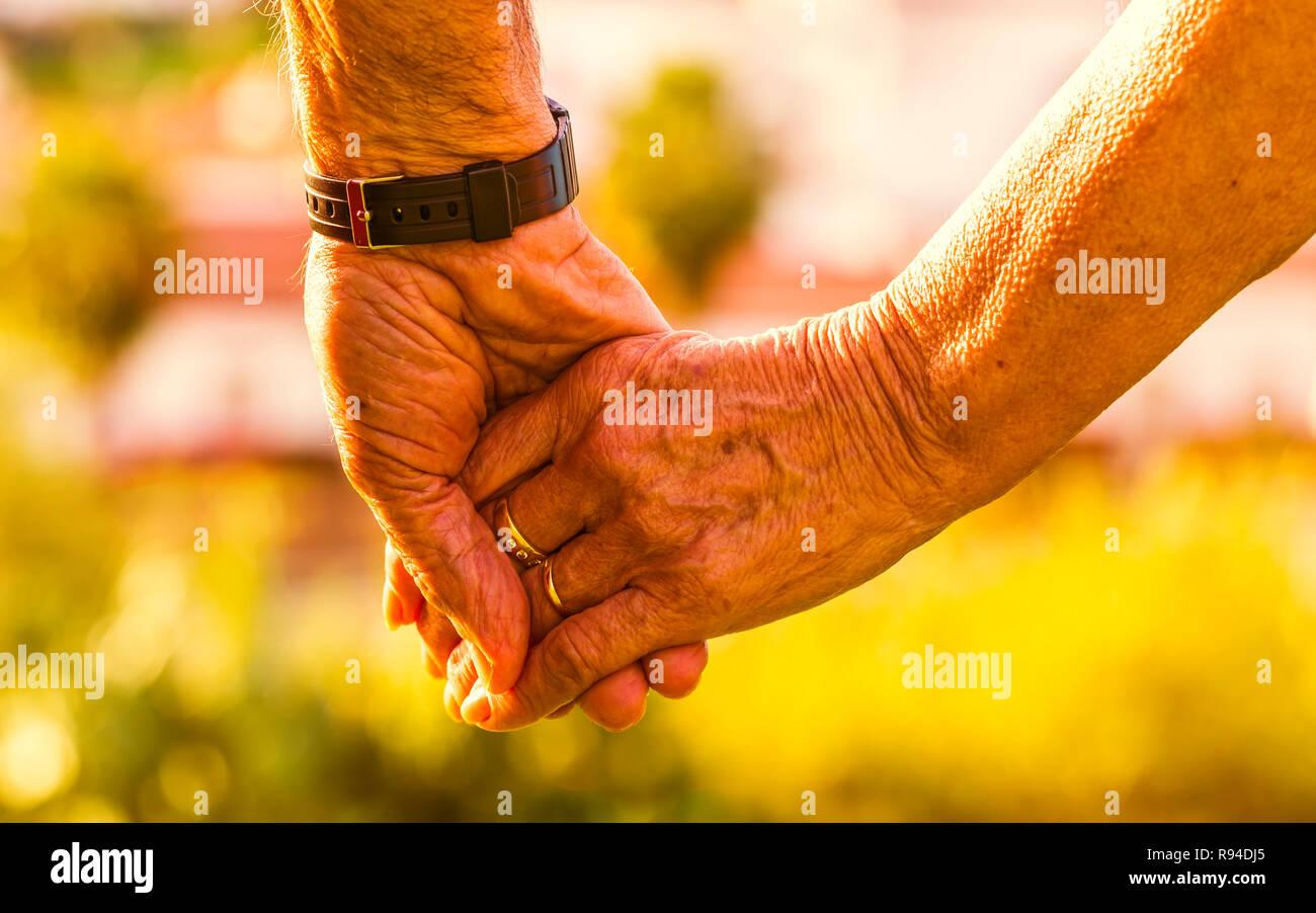 Captura recortada de la pareja de ancianos tomados de la mano exterior con la luz del atardecer. Se centran en las manos Foto de stock