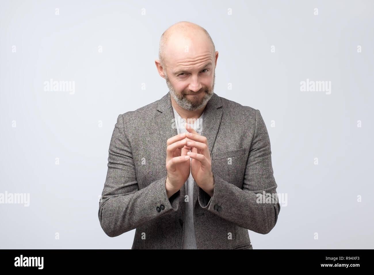 Astuto hombre maduro difícil pensar con la mano juntos sobre fondo blanco. Imagen De Stock