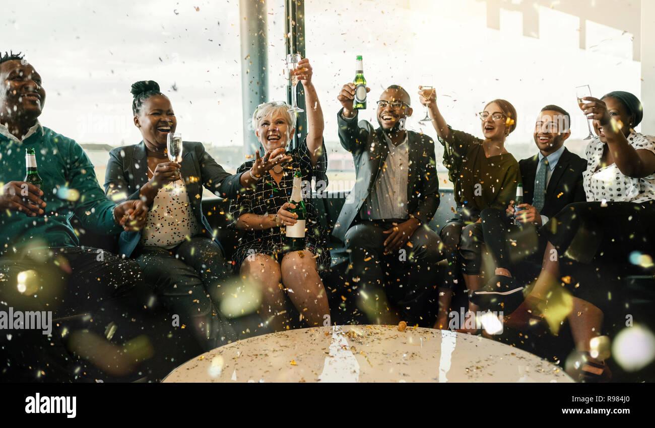Un festivo grupo multiétnico de gente sonriente, brindando con vino espumoso y cerveza. Celebrando el final del año y para el nuevo año ahe Foto de stock