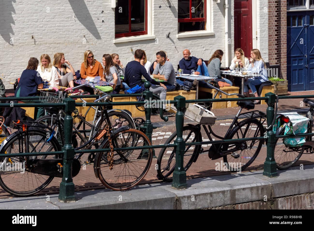 Jóvenes sentados fuera de Festina lente cafe en Ámsterdam, Países Bajos Imagen De Stock