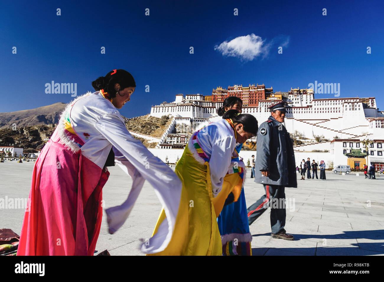 Lhasa, región autónoma del Tíbet, China : un policía chino camina últimos tres mujeres tibetanas probando trajes tradicionales junto al palacio de Potala. Fir Imagen De Stock