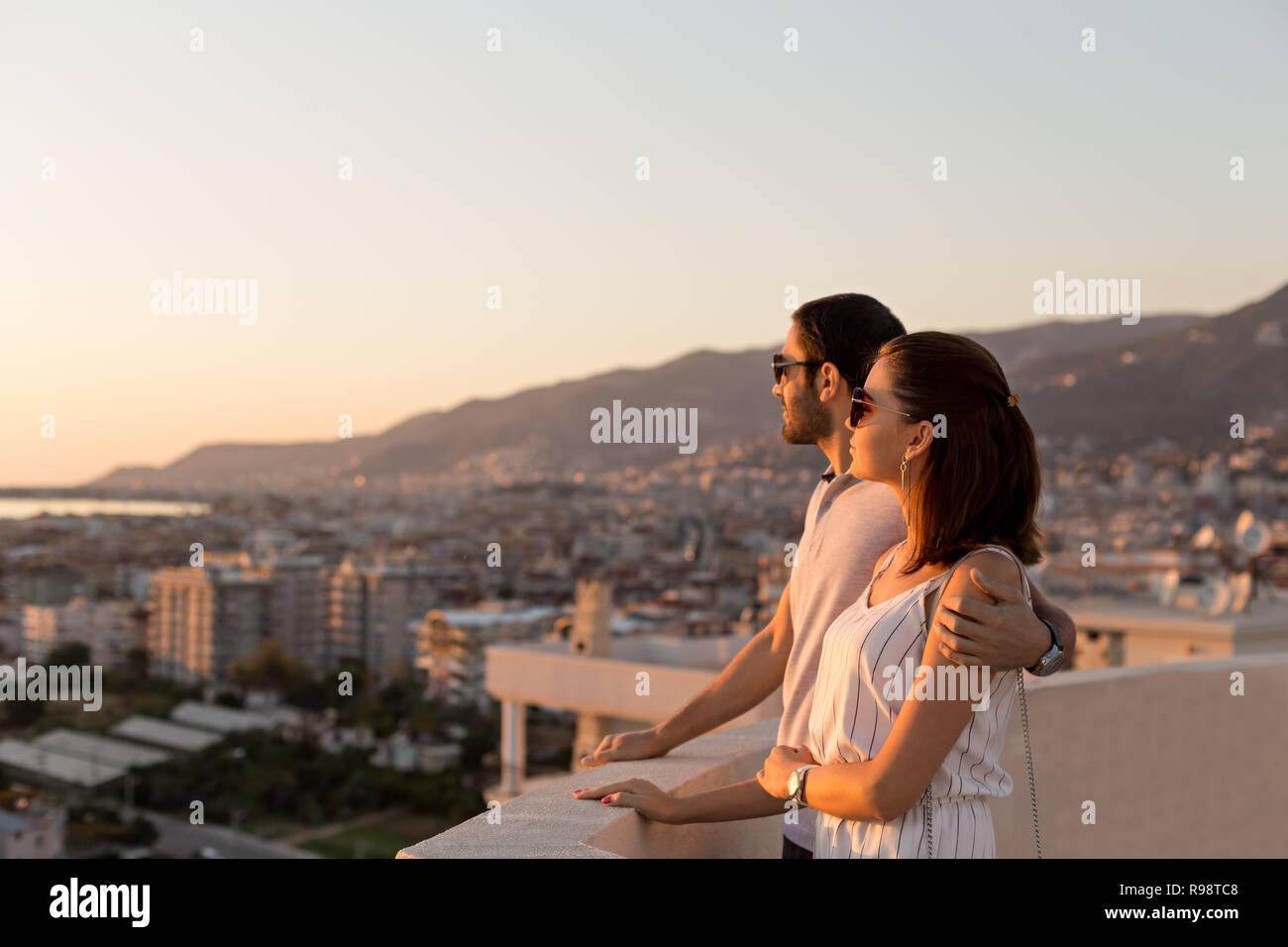 Disparo sideview horizontal de una joven pareja en atuendo de verano a disfrutar de la ciudad y vistas a la montaña desde la terraza de la azotea. Copie el espacio. Foto de stock