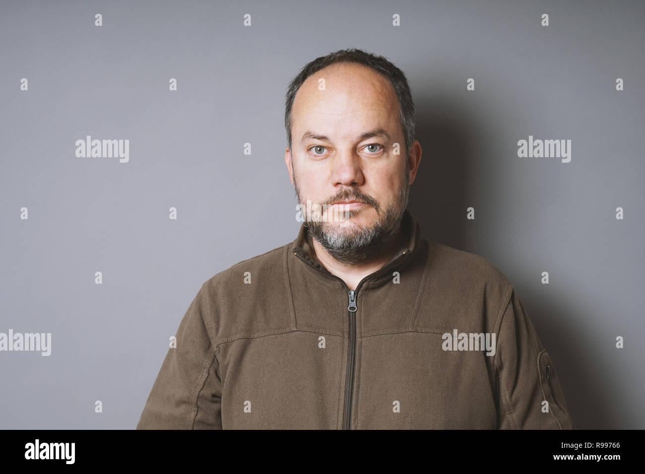 Un varón de mediana edad en su 40s con el cabello oscuro corto y encanecimiento barba contra la pared gris con espacio de copia Imagen De Stock