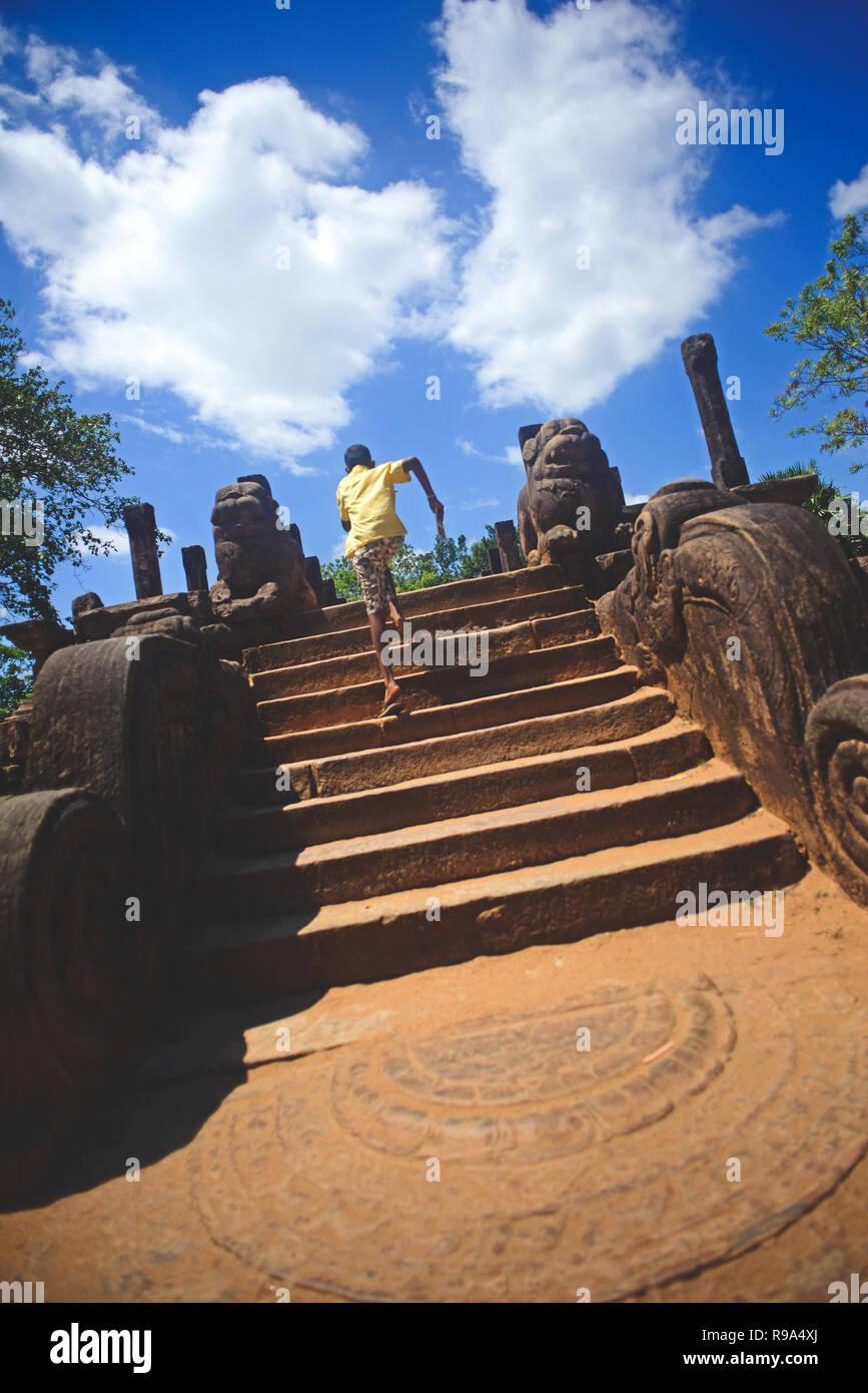 Niño corriendo las escaleras en la sala de audiencias, en la antigua ciudad de Polonnaruwa, Sri Lanka Foto de stock