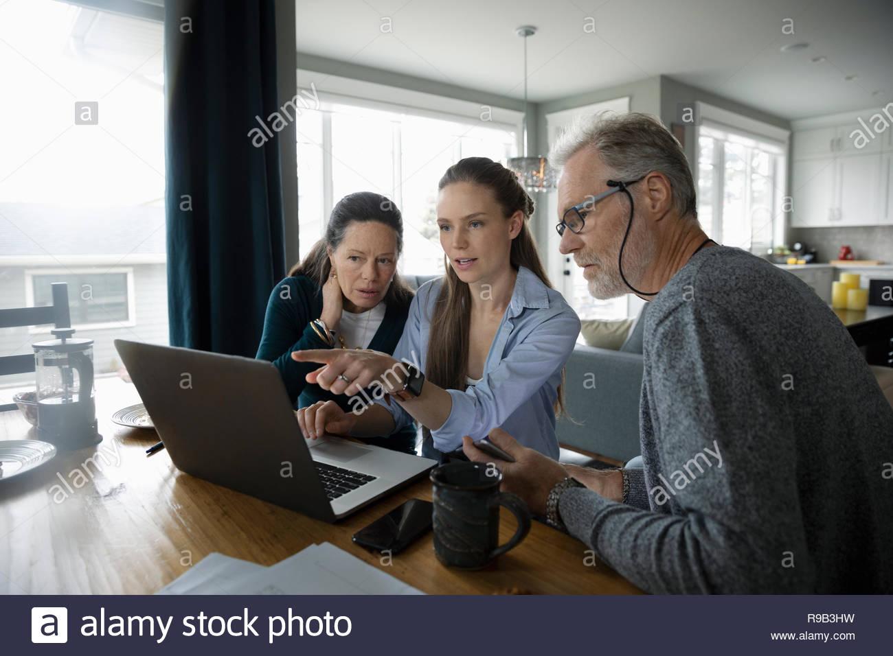 Los padres y adultos hija utilizando el portátil en la mesa de comedor Imagen De Stock