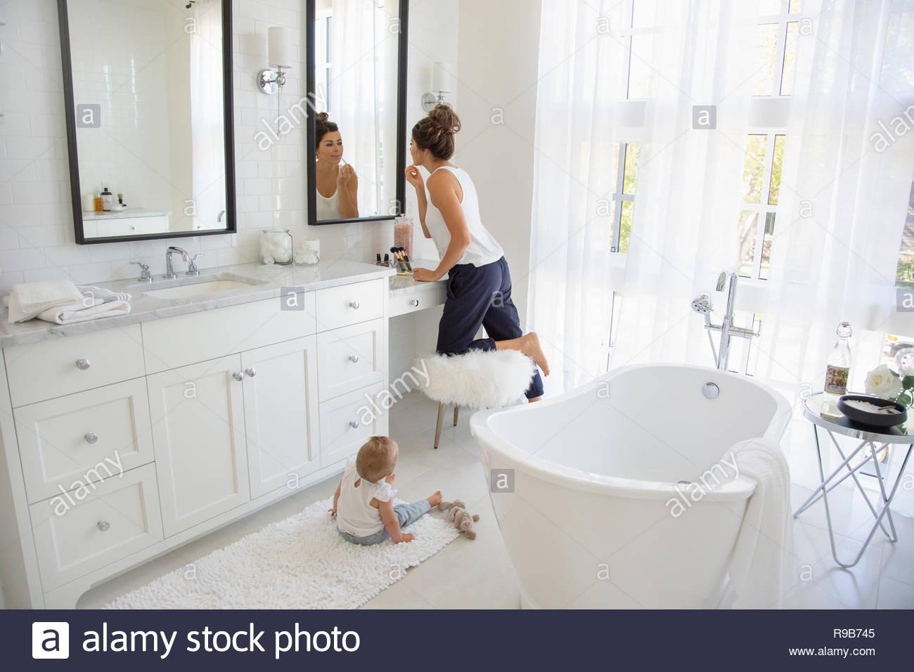 Hija ve la madre al maquillaje en el espejo del baño Imagen De Stock
